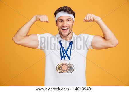 Cheerful young spotrsman with three medals showing biceps over yellow background