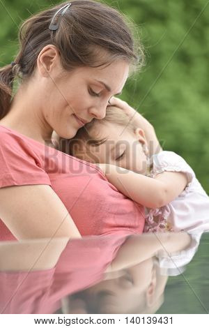 Closeup of woman breast-feeding 2-year-old baby girl