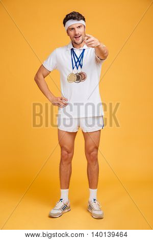 Handsome young spotrsman with three medals standing and pointing on you over yellow background
