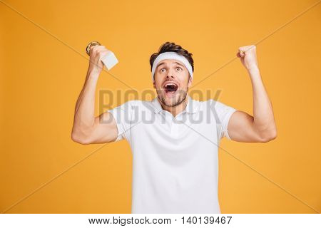 Happy excited young sportsman holding trophy cup and shouting over yellow background