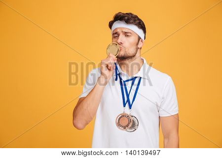 Portrait of funny young spotrsman standing and kissing his medal over yellow background