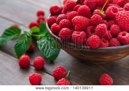 Red fresh raspberries on brown rustic wood background. Bowl with natural ripe organic berries with peduncles and green leaves on wooden table closeup
