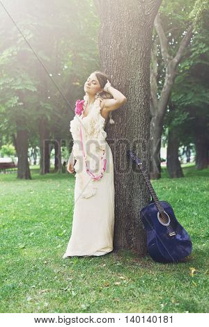 Fashion portrait of beautiful boho style smiling girl in long dress with blue acoustic guitar in sun warm light. Female standing posing near tree in park, female musician. Woman and musical instrument