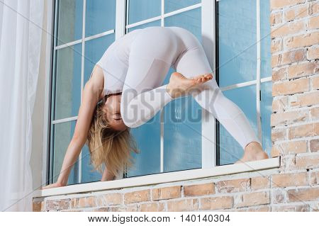 Young Beautiful Woman Practicing Yoga Doing Exercise On A Windowsill