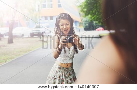Young asian girl taking photo of her friend outdoors with digital camera. Young female tourist in boho fashion clothes, laughing and having fun in summer park. Travelling together, lifestyle portrait.