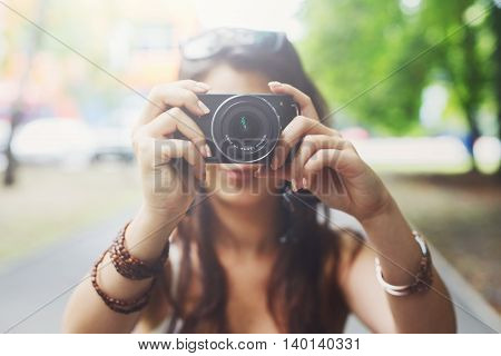 Young asian girl taking photo outdoors with digital camera. Selective focus at lens, unrecognizable person. Young female tourist having fun in summer park. Lifestyle portrait, soft toned