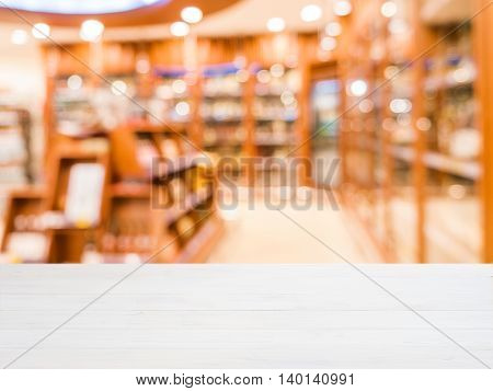 White wooden board empty table in front of blurred background. Perspective white wood over blur in department of alcoholic drinks in supermarket - Mockup for display or montage your products