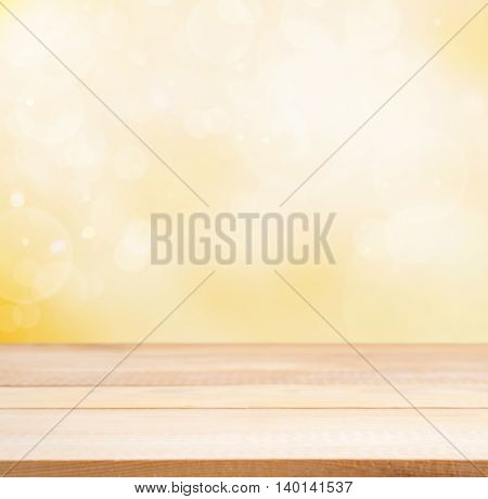 Wooden board empty table in abstract gold background with bokeh. Perspective light wood board over blurred orange background - mockup for display of product