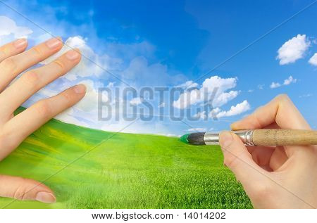 Hands with brush drawing green meadow and blue sky