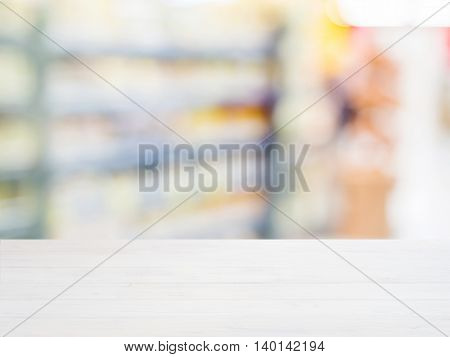 White wooden board empty table in front of blurred background. Perspective whitewood over blur in supermarket - can be used for display or montage your products. Mockup for display of product.