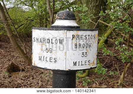 Old-fashioned milepost along a public canal footpath through Stoke-on-Trent, Staffordshire, part of a wider network of Midlands and Northeast England canal paths.