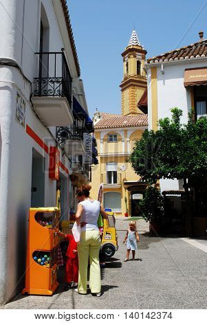 ESTEPONA, SPAIN - JULY 18, 2008 - Old town street with church spire to the rear and a woman with children looking at a vending machine Estepona Malaga Province Andalucia Spain Western Europe, July 18, 2008.