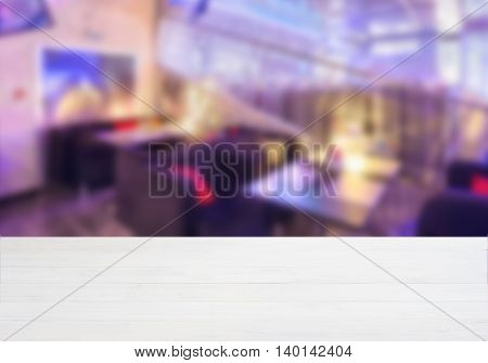 White ooden board empty table in front of blurred background. Perspective whitewood over blur in cafe interior - can be used for display or montage your products. Mockup your products