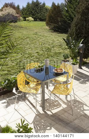Table and four yellow chairs in the yard behind the house with a beautiful garden view