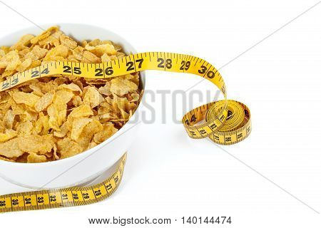 corn flakes with yellow measuring tape isolated on white background