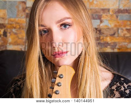 Close up portrait of attractive young girl in black lace shirt sitting in chair with guitar brick background