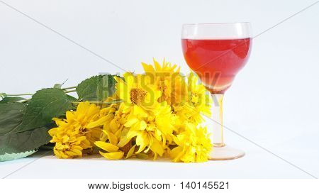 Yellow flowers lie on a white background next to a glass of red wine
