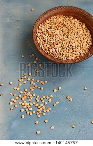 Green lentil in wooden bowl on blue background