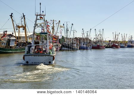 Buesum, Germany - July 20, 2016: Fishing boats moored at the south pier of the fishing port, rescue cruiser THEODOR STORM?? in foreground departing to the North Sea.