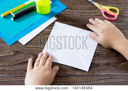 The Child Holds A Paper Strip Square And Fold Him Twice. The Child Makes Crafts Out Of Paper Boat. G