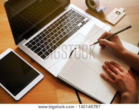 Hand business woman using a laptop and makes an entry in his notebook.