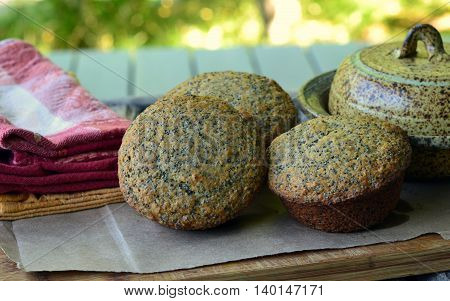 Muffins with Poppy Seeds and Wheat Germ: Shown on a wooden board, brown paper, napkins and butter dish.