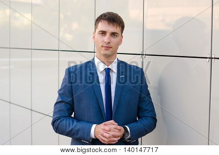 Portrait of a young successful man economist standing in modern office interior confident male dressed in luxury corporate clothes using digital tablet during work break