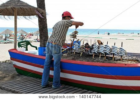 ESTEPONA, SPAIN - JULY 18, 2008 - Restaurant worker cooking sardines on a boat barbecue along the beach Estepona Malaga Province Andalusia Spain Western Europe, July 8, 2008.