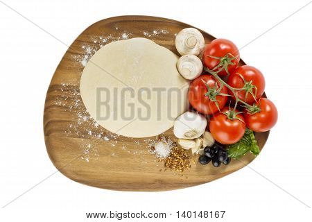 pizza ingredients with dough on chopping board