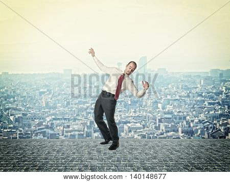 businessman in balance pose urban town background