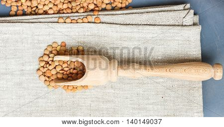 raw lentils on a wooden spoon on a linen cloth