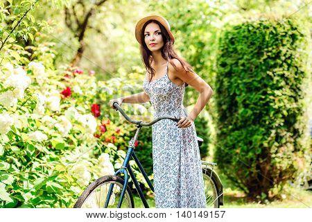 Beautiful yoang woman riding on bike on nature garden background