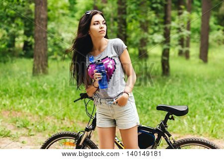 Young woman drinking water after riding an exercise bike on tnature park forest