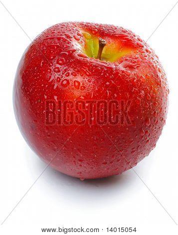 Una manzana húmeda sobre la superficie de vidrio sobre blanco