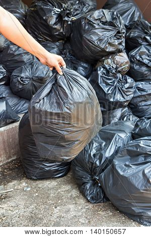 Hand Carrying Garbage Bag Over Pile Of Garbage Bags In A Dump