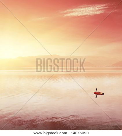 Alone fisherman in boat on huge lake under sunset light