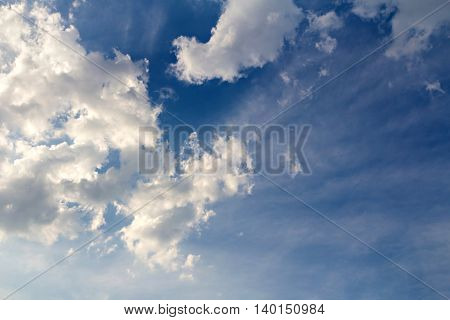 Clouds and sun beam on blue sky background