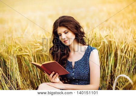 Portrait of cute pretty happy young woman with basket in dress reading book sitting on a grass in field. Sunny morning. harvest season autumn nature healthy concept