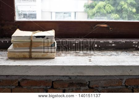 The stack of book on old plank at the windowsill