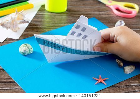Crafts Paper Boat, Origami. Glue, Scissors, Paper, Starfish And Seashells On A Wooden Table. Childre
