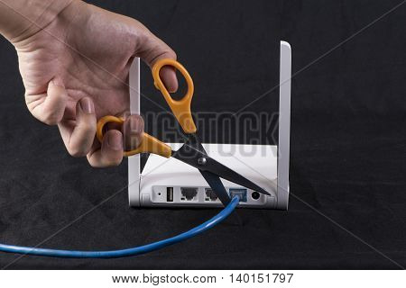 Hand cutting internet cable of router communication concept