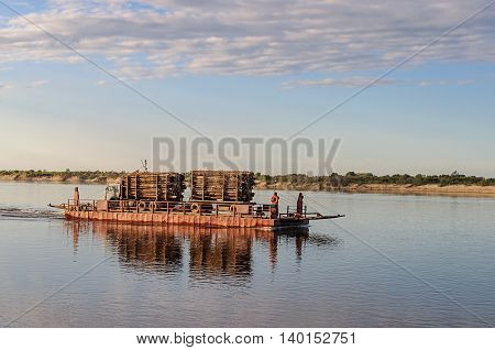 River ferry with timber on the Northern Dvina near Krasnoborsk Russia. Sunset