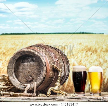 Glasses of  beer and ale barrel on the wooden table. Craft brewery. The field of wheat on the background.