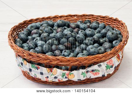 Fresh blueberries in a wooden basket on a light background