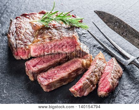Medium Ribeye steak with spices on the graphite tray.