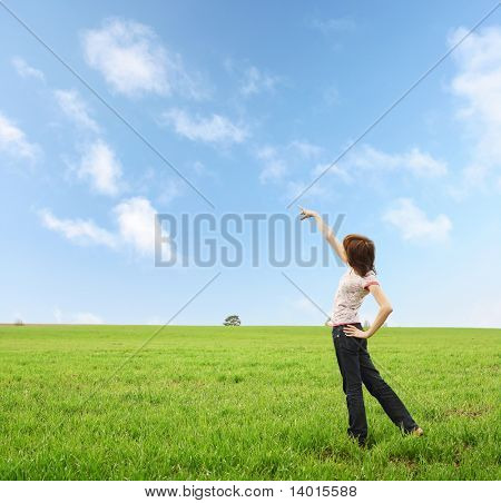 Young woman on meadow with green grass and blue sky