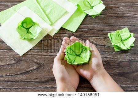 The Child Keep On Hand Crafts Out Of Paper Water Lily. Paper Napkins On A Wooden Table. Children's A