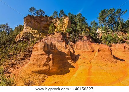 Steps for tourists on a steep slope. Unique red and orange hills in the province of Languedoc - Roussillon, France