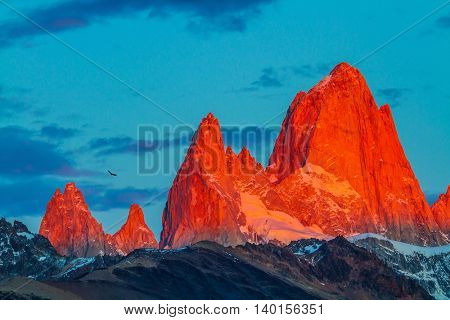 Sharp tops fantastically cliffs Fitz Roy illuminates the crimson sunset. Patagonia in February