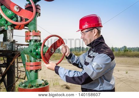 Worker repairing well head valve wearing red helmet and work clothes in the oilfield. Oil and gas concept.